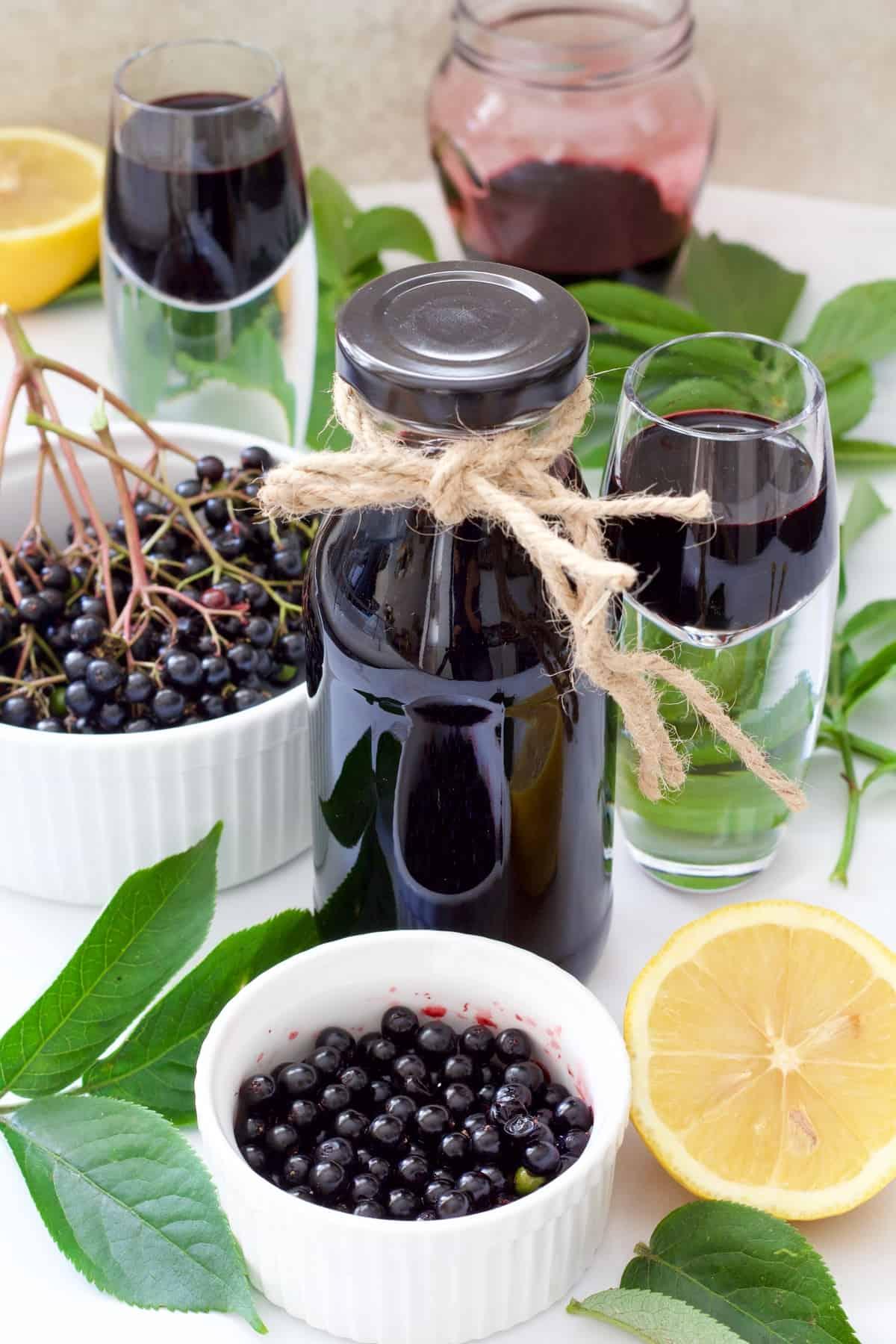 Fresh elderberries in bowls, syrup in bottle and shot glasses.