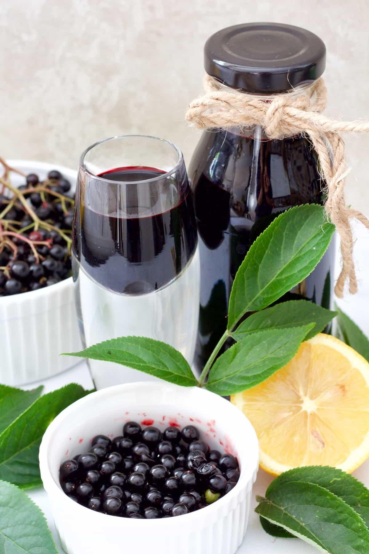 Small bottle & shot glass w with elderberry syrup, fresh elderberries.