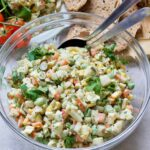 Russian salad in a bowl with serving spoons.