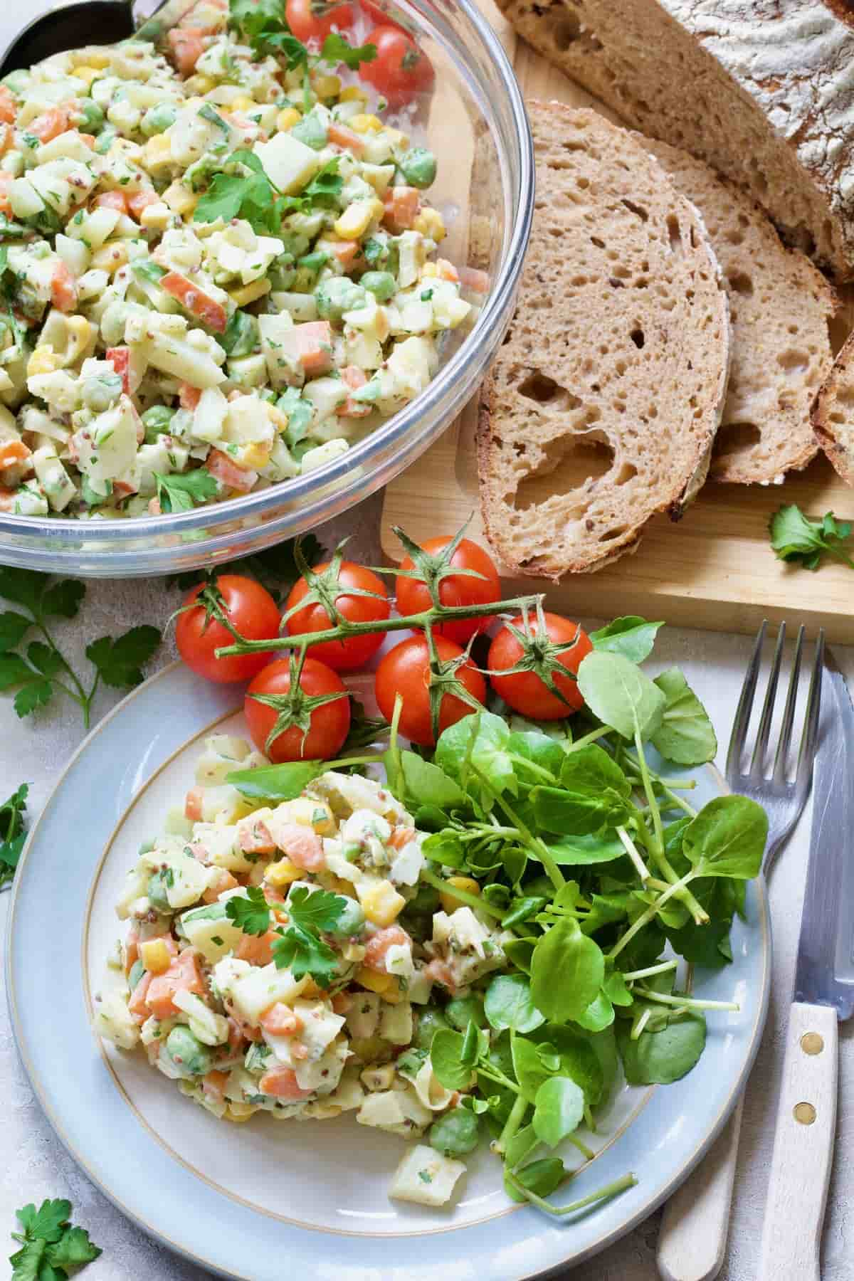 Russian salad portion with watercress and tomatoes.