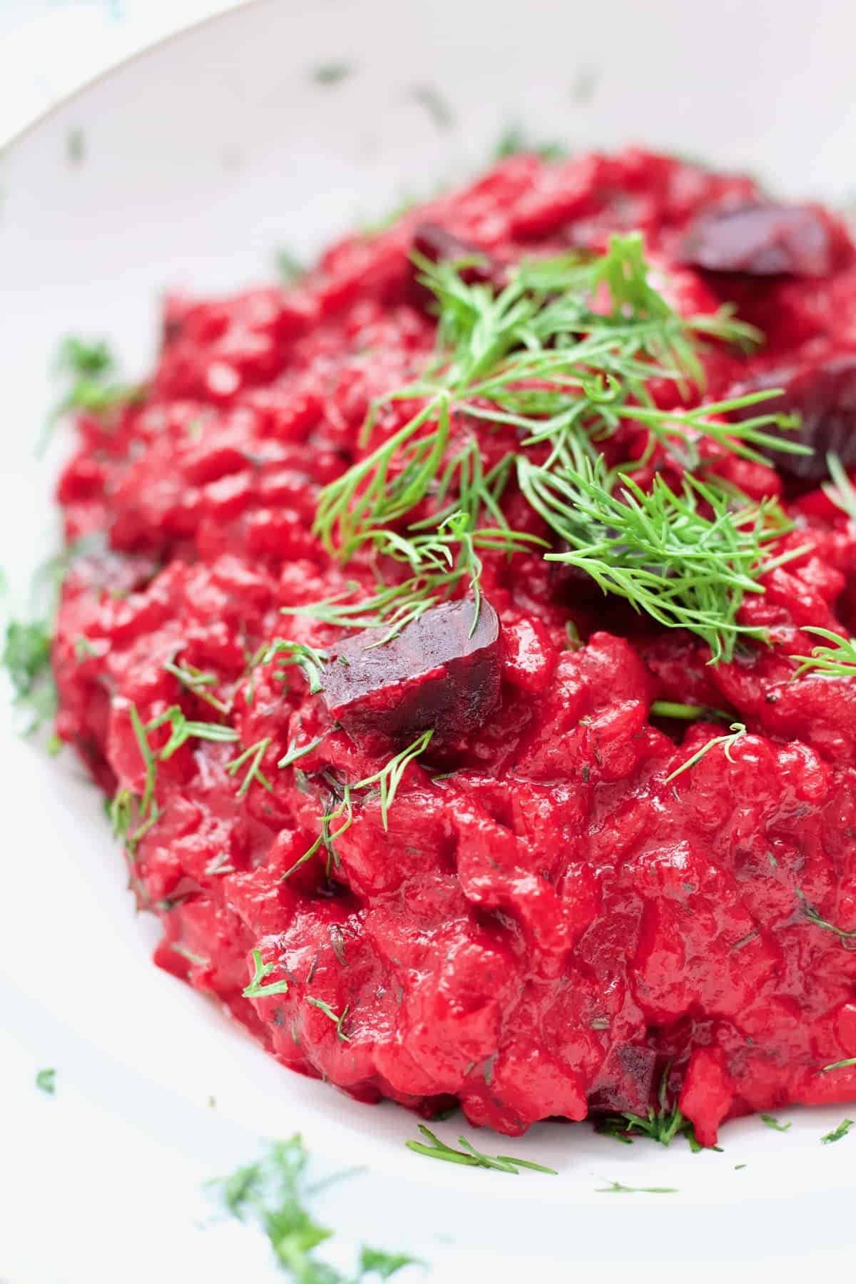 Close up of beetroot risotto portion with beetroot chunks and dill.